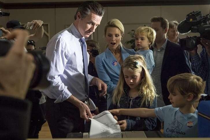 Gavin Newsom, Democratic candidate for governor of California, votes as his wife Jennifer Siebel Newsom and children watch at a polling location in Larkspur, California, U.S., on Tuesday, June 5, 2018. Democrats are facing a potentially destructive California primary vote Tuesday for an unlikely reason: too many viable candidates are running for the same U.S. House seats. Photographer: David Paul Morris/Bloomberg