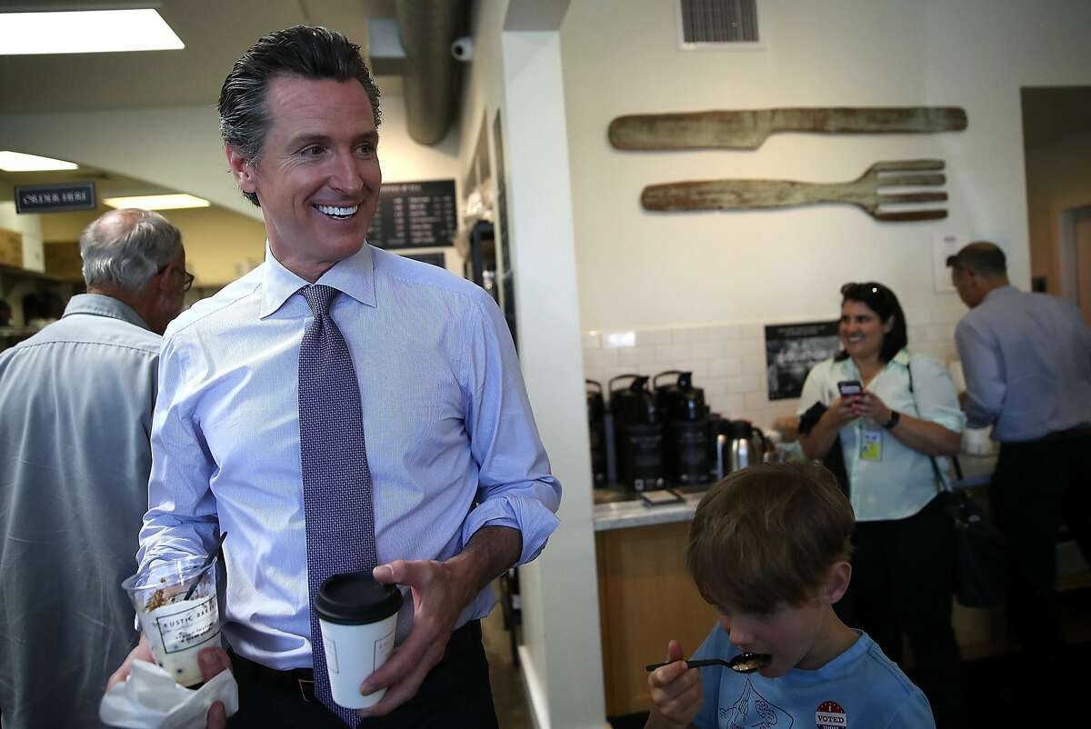Democratic California gubernatorial candidate Lt. Gov. Gavin Newsom (L) smiles as he walks through Rustic Bakery on June 5, 2018 in Larkspur, California. California Lt. Gov. Gavin Newson cast his ballot as California voters are heading to the polls to vote in the primary election. Newsom is expected to claim the top spot in the California gubernatorial primary election ahead of republican candidate John Cox and former Los Angeles mayor Antonio Villaraigosa, a democrat.