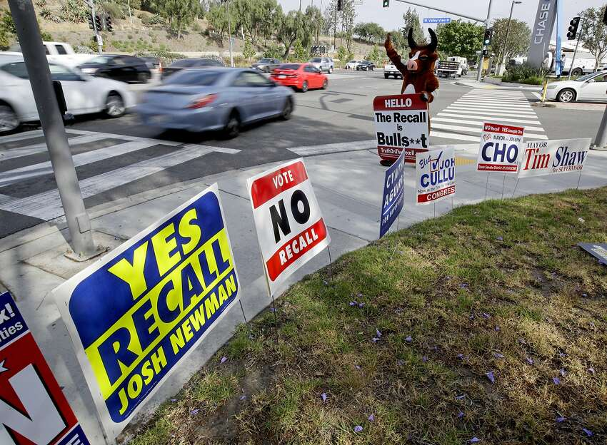 A person in a bull suit, standing amid campaign signs, urges voters to reject the recall campaign launched against Democratic state Sen. Josh Newman on a street in Fullerton on May 30. On Tuesday, voters in his Orange County district recalled Newman.