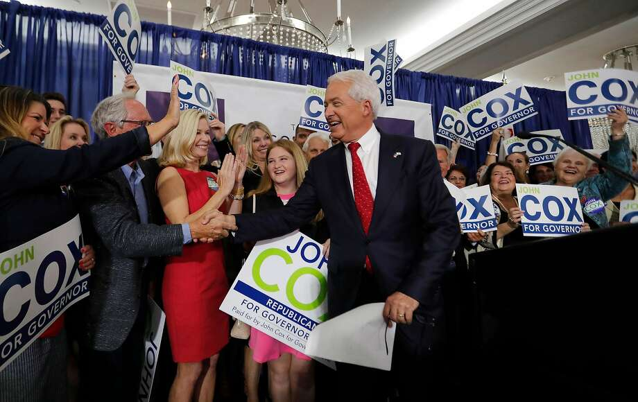 Click through the gallery to learn about John Cox, pictured here with his wife, Sarah, and daughter Julianne, 13, at his primary election night party in San Diego. Photo: Allen J. Schaben, TNS