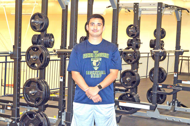 Father McGivney athletic director Jeff Oller poses in the school's weight room, which opened last summer. FMCHS continues to add to the list of sports that it offers.