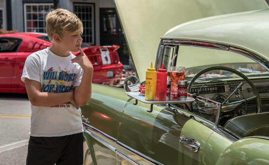 A patron at last year's All-Wheels Drive-In Car Show checks out one of the vintage rides on display. Photo:       Andrew Dobson | For The Telegraph