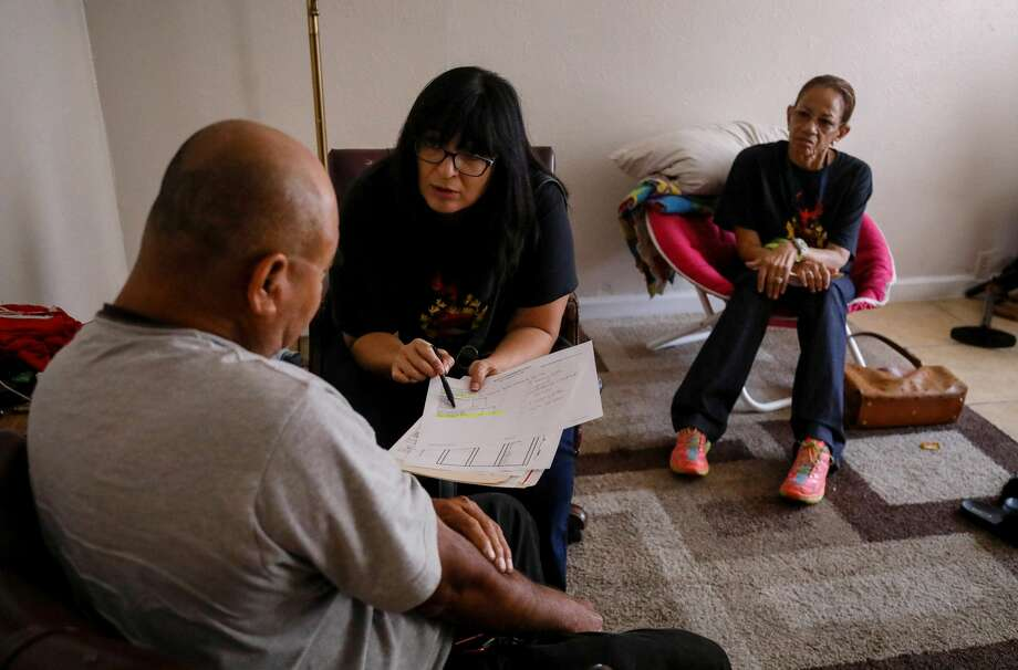 """Where is your daughter?"" principal Diana Del Pilar asks a student's father in his Gulfton apartment. Photo: Jon Shapley"