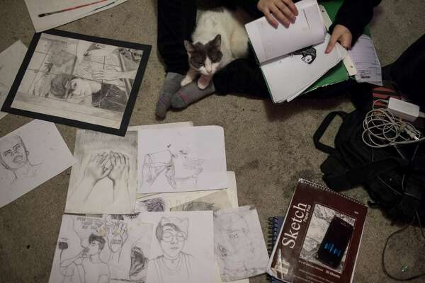 Dakota sits with his cat Pepper as he flips through his artwork. in one portrait, the version of him his family wants -- the female body of a girl named Shelby -- smiles through her makeup as she sees who she really wants to be: Dakota.