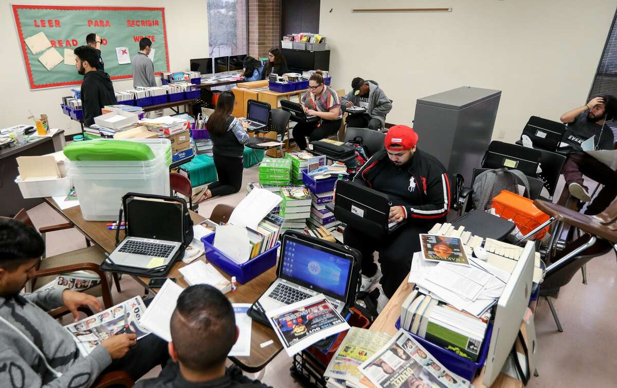 On the last day of class in December, several students hurriedly finish final projects, while others help arrange the room for cleaning over winter break.