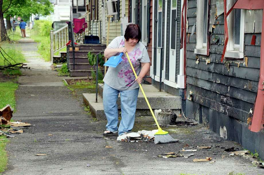 Debbie Faraci of 602 Fourth Ave., clears fire debris from in front of her mother's home next door at 600 Fourth Ave., Wednesday June 6, 2018 in Troy, NY. Faraci and her husband were able to rescue her elderly mother after a suspected arson attempt over night.  (John Carl D'Annibale/Times Union) Photo: John Carl D'Annibale, Albany Times Union / 20044009A