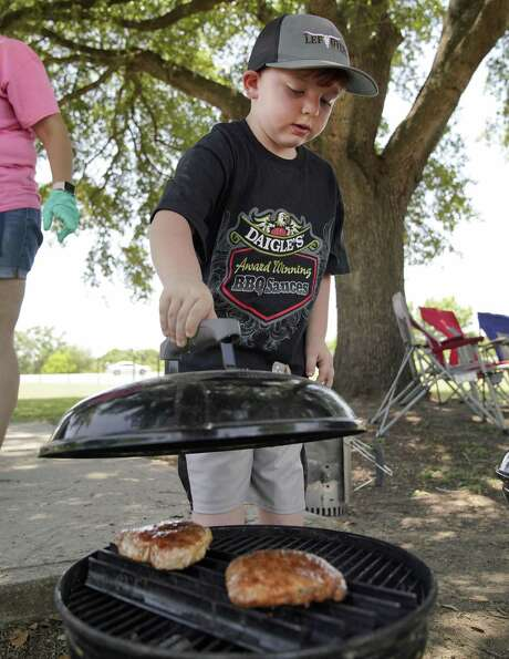 Jacob Kempker, 5, places the lid on his pork chops after flipping them on a grill. Photo: Darren Abate /For The Express-News