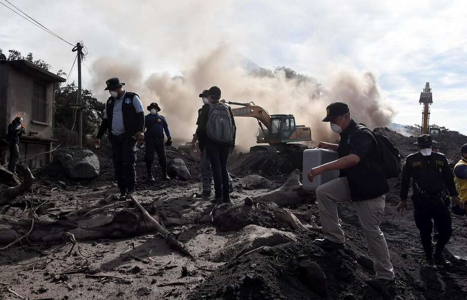 Police officers search for victims of the Fuego Volcano eruption in the village of San Miguel Los Lotes. Photo: Johan Ordonez / AFP / Getty Images
