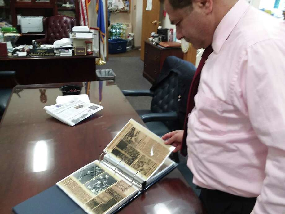 Mayor David Cassetti looks over the scrapbook dedicated to the Ansonia Chargers' 1976 season Photo: GREG MARTIN /ANSONIA CITY HALL /