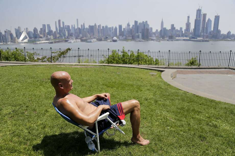 FILE - In this Tuesday, May 15, 2018 file photo, Rick Stewart sits in the sunshine with the New York City skyline in the background, in a park in Weehawken, N.J. According to weather records released on Wednesday, June 6, 2018, May reached a record 65.4 degrees in the continental United States, which is 5.2 degrees above the 20th century average. (AP Photo/Seth Wenig) Photo: Seth Wenig, Associated Press