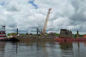 Crews lift up portions of a sunken barge from the bottom of the Hudson River at the Port of Coeymans on June 6, 2018.