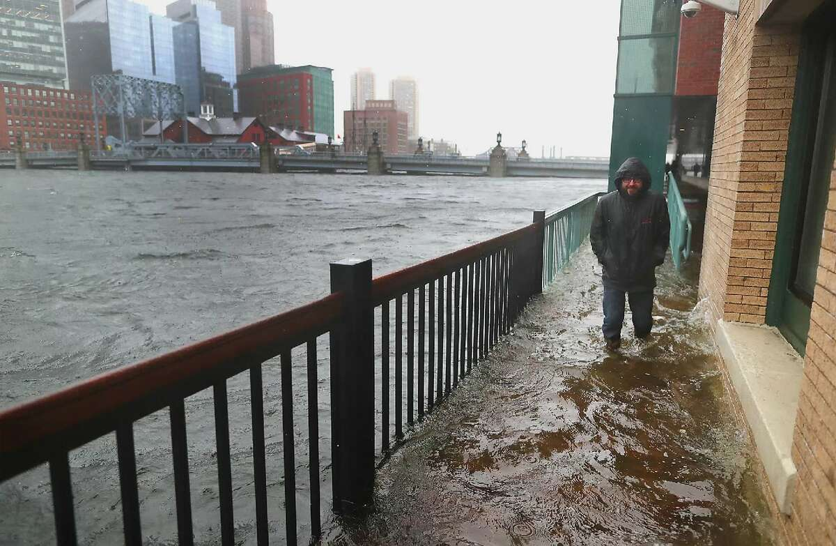 In this March 2, 2018 photo, a man walks through a flooded sidewalk in Boston's Seaport District. General Electric is building its new world headquarters and Amazon is bringing in thousands of new workers to Boston�s booming Seaport District. Trendy restaurants and apartments have gone up virtually overnight. But after bad flooding during a storm this past winter, critics wonder whether it was a bright idea to invest so much on a man-made peninsula barely above sea level. (John Tlumacki, The Boston Globe via AP)
