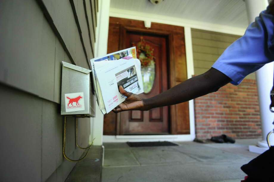 Eugenia Titus, a Stamford postal worker, delivers mail to a house on Yale Ct. with a dog on Thursday, May 19, 2016. Postal Service is changing procedures to protect letter carriers from dog attacks, including adding dog stickers to mailboxes to alert new mail carriers of the canine inside. Photo: Michael Cummo / Hearst Connecticut Media / Stamford Advocate