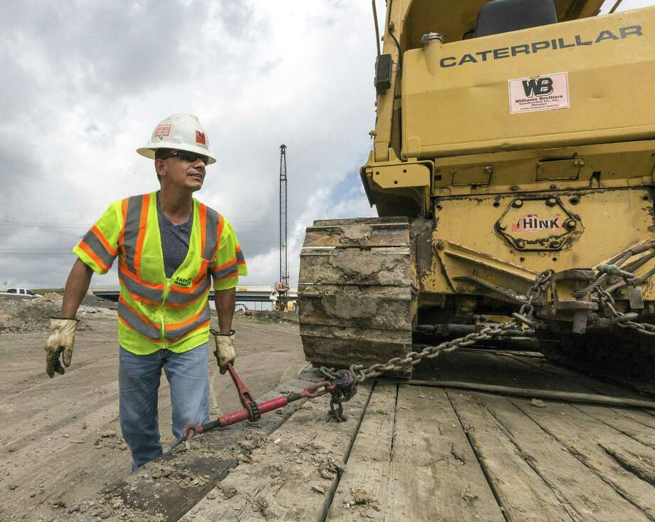 Juan Casco finishes tying down a tractor to a flatbed beside the northbound lane of Interstate 45 during widening work north of NASA Road 1 on May 5, 2015. Photo: Craig Hartley, Freelance / For The Chronicle / Copyright: Craig H. Hartley