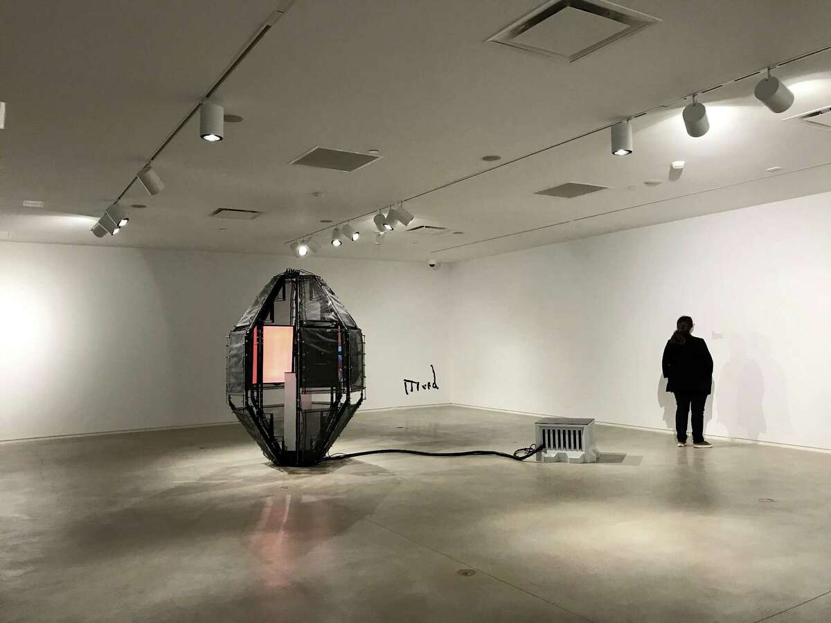 """Felix Kalmenson's video installation """"Atlas"""" is built into a capsule-like structure around a pedestal containing a Soviet calendar wristwatch from the 1980s, which is stopped at the year 2000."""