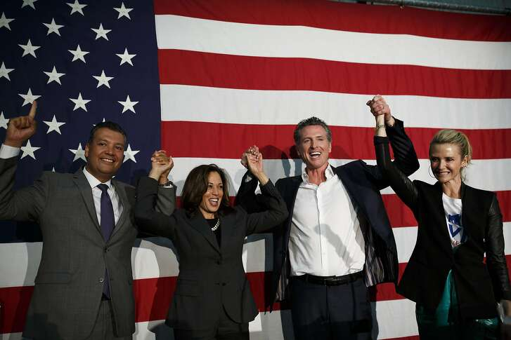 Alex Padilla, California secretary of state, from left, Senator Kamala Harris, a Democrat from California, Gavin Newsom, Democratic candidate for governor of California, and wife Jennifer Newsom raise their hands during a rally in Burbank, California, U.S., on Wednesday, May 30, 2018. The Democratic candidates running to replace Governor Jerry Brown -- Lieutenant Governor Newsom, former Los Mayor Antonio Villaraigosa and State Treasurer John Chiang-- have pledged to protect the rights of undocumented immigrants. Photographer: Patrick T. Fallon/Bloomberg