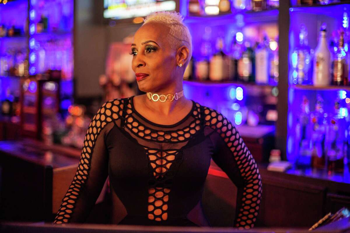 Dee Lewis, a bartender at Dreams Bar & Lounge poses for a portrait behind the bar.