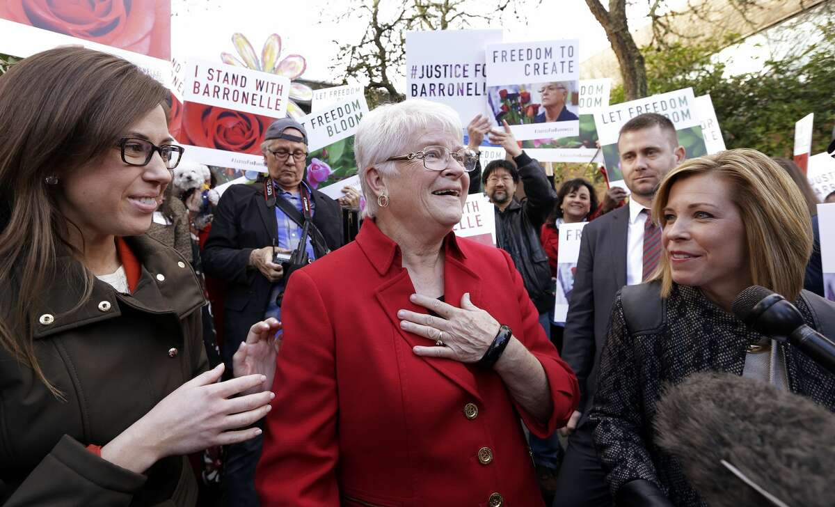 Barronelle Stutzman, center, a Richland, Wash., florist who was fined for denying service to a gay couple in 2013, reacts to being surrounded by supporters after a hearing before Washington's Supreme Court, Tuesday, Nov. 15, 2016, in Bellevue, Wash. Stutzman was sued for refusing to provide services for a same sex-wedding and says she was exercising her First Amendment rights, but justices questioned whether ruling in her favor would mean other businesses could turn away customers based on racial or other grounds. (AP Photo/Elaine Thompson)