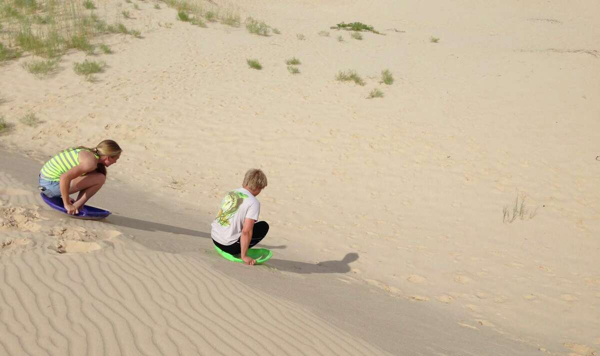 Children surfing the dunes at Monahans Sandhills State Park, about 30 miles west of Odessa.