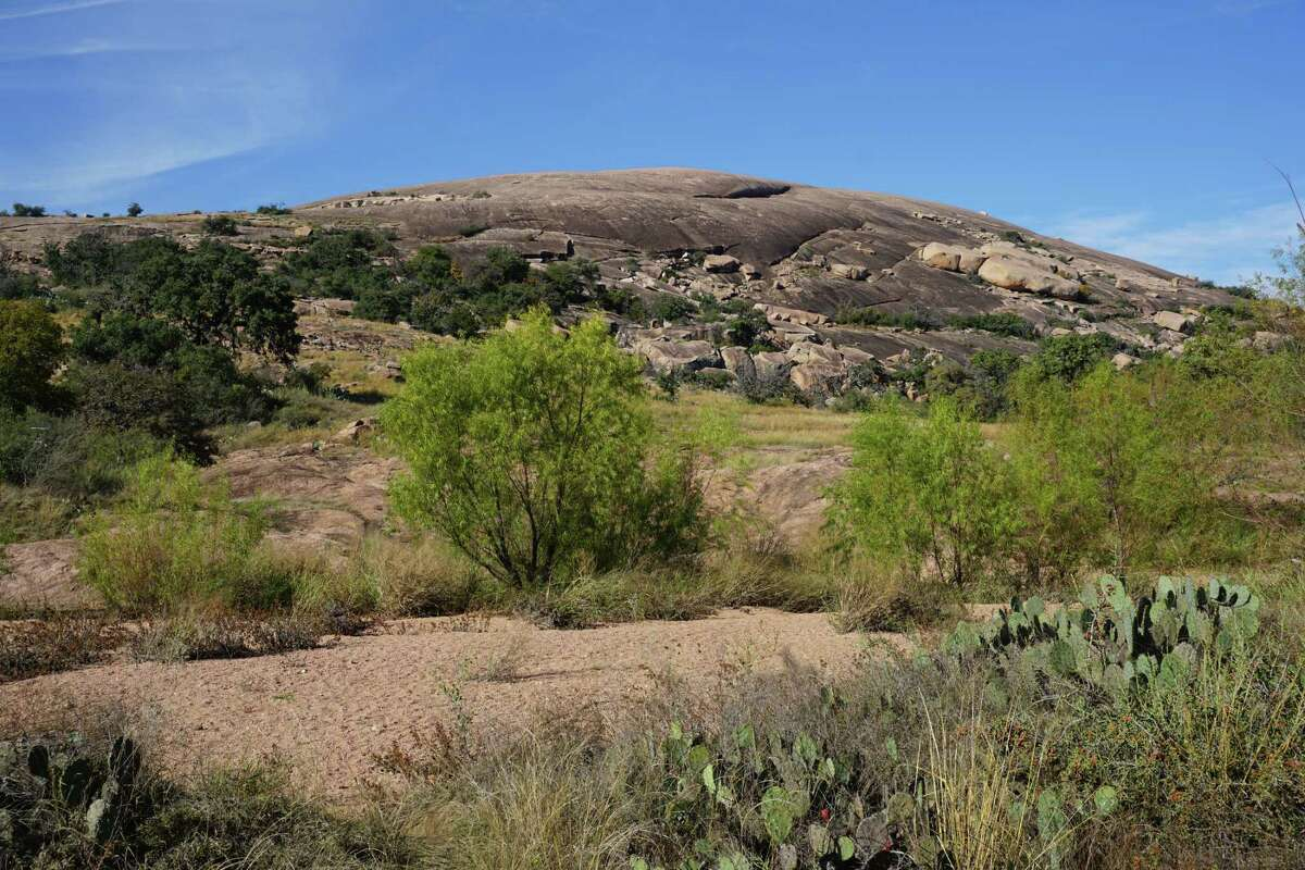 The summit of Enchanted Rock State Natural Area is seen in the distance, a 425-foot change in elevation from where the trail begins. Enchanted Rock is a popular destination for Come Into The Outside hikes.