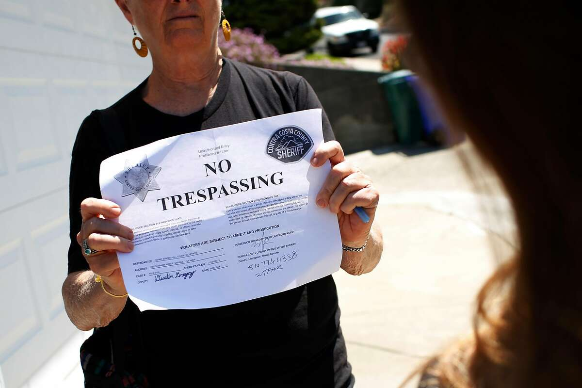 Marilyn Langlois (left), with Alliance of Californians for Community Empowerment, shows a no trespassing notice given to Genny Zentella (not shown) when she was removed from her home earlier in the morning on Tuesday, June 5, 2018 in San Pablo, Calif. A stay of execution had expired at 6 a.m. the day before.