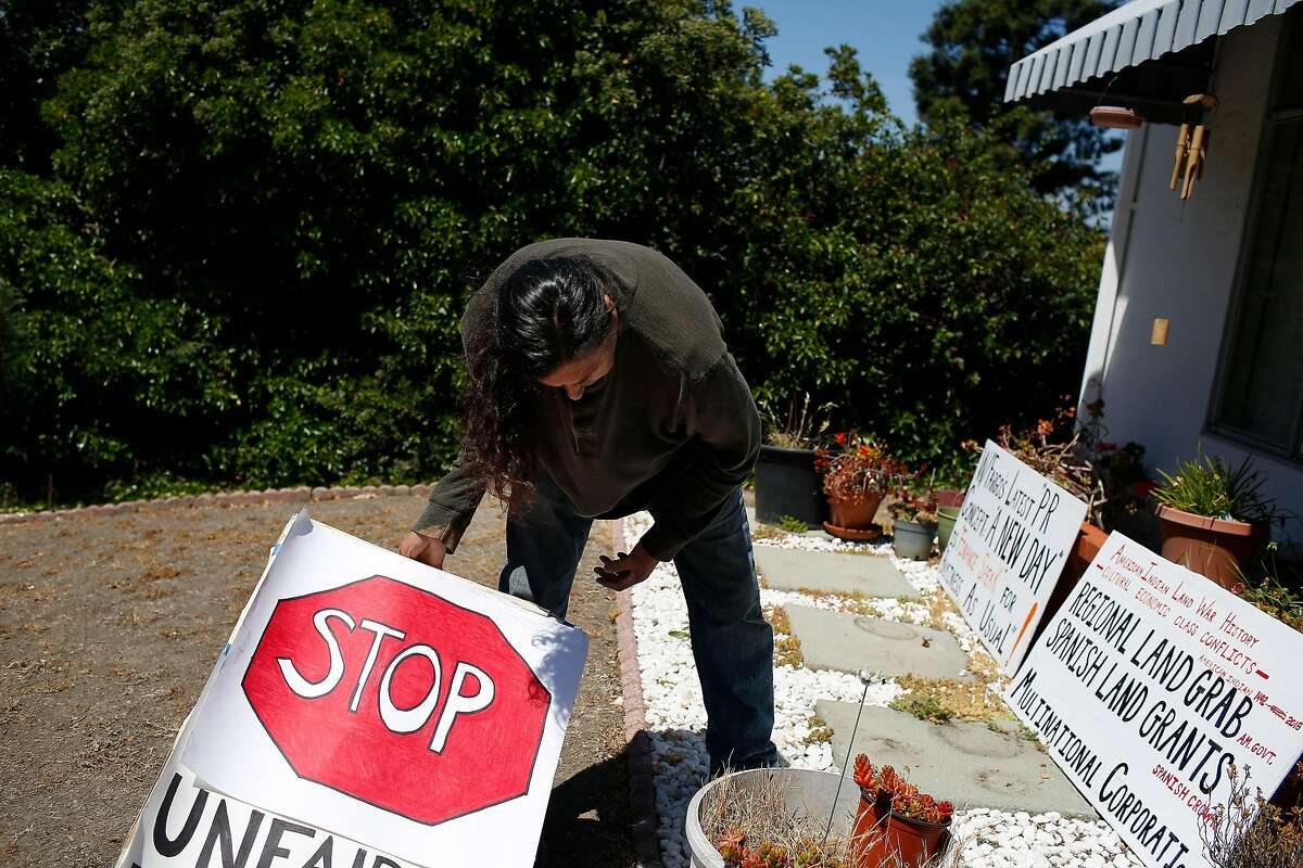 Ricardo Davis, friend of Genny Zentella, gathers signs, used in an earlier action, together which after Zentella was removed from her home earlier in the morning on Tuesday, June 5, 2018 in San Pablo, Calif. A stay of execution had expired at 6 a.m. the day before.