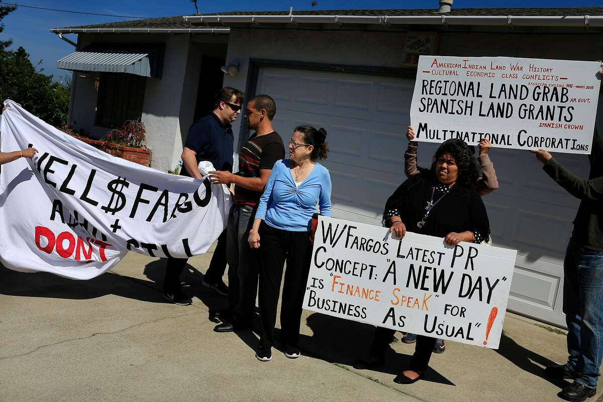 Genny Zentella (center in blue shirt) stands with supporters and their signs as they gather to take a photo shortly after she was removed from her home earlier in the morning on Tuesday, June 5, 2018 in San Pablo, Calif. A stay of execution had expired at 6 a.m. the day before.