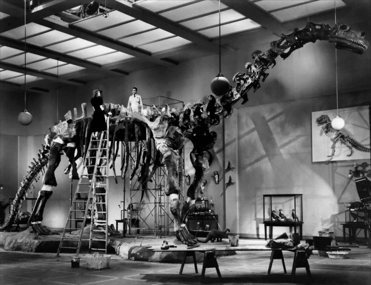 """L-R: Katharine Hepburn and Cary Grant atop the bronotosaurus in """"Bringing Up Baby"""" (1938). Photo courtesy of Warner Home Video."""