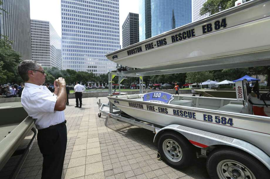Houston Fire Department Deputy Chief Public Information Officer Richard Galvan takes a photograph of the 100 Club sign and the donated rescue boats at City Hall on Wednesday, June 6, 2018, in Houston. The 100 Club donated 14 rescue boats to the Houston Police Department, HFD and the Harris County Sheriff's Office  HPD. ( Yi-Chin Lee / Houston Chronicle ) Photo: Yi-Chin Lee / Houston Chronicle / © 2018 Houston Chronicle