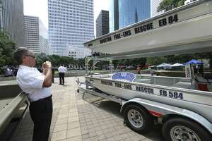 Houston Fire Department Deputy Chief Public Information Officer Richard Galvan takes a photograph of the 100 Club sign and the donated rescue boats at City Hall on Wednesday, June 6, 2018, in Houston. The 100 Club donated 14 rescue boats to the Houston Police Department, HFD and the Harris County Sheriff's Office  HPD. ( Yi-Chin Lee / Houston Chronicle )