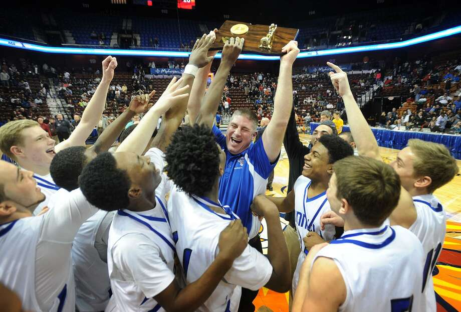 Bunnell head coach Pat Yerina holds the state championship trophy aloft as he celebrates with his players following their defeat of Naugatuck in the Class L boys basketball state championship game at the Mohegan Sun Arena in Uncasville, CT on Sunday, March 22, 2015. Photo: Brian A. Pounds / Brian A. Pounds / Connecticut Post