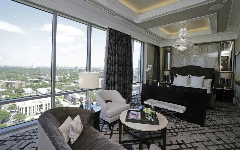 The master bedroom has a view of downtown Houston. Its furnishings include a small sofa and chair in a seating area, plus a king-size upholstered bed. Photo: Melissa Phillip, Staff / Houston Chronicle / © 2018 Houston Chronicle
