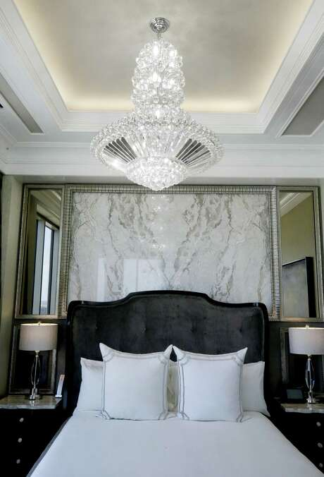 This tiered chandelier hangs over the king-size bed in the master suite. Photo: Melissa Phillip, Staff / Houston Chronicle / © 2018 Houston Chronicle