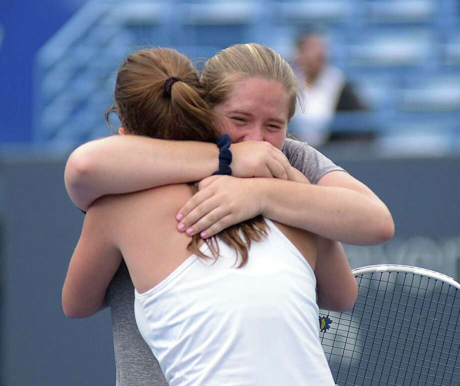 Kristin Butler, rear, of Staples embraces teammate Hannah Bjorkman after the two won the State Open girls tennis doubles champinonship with a 6-4, 0-6, 7-6 (10-8) win over Stamford at the Connecticut Tennis Center on Wednesday. Photo: John Nash / Hearst Connecticut Media