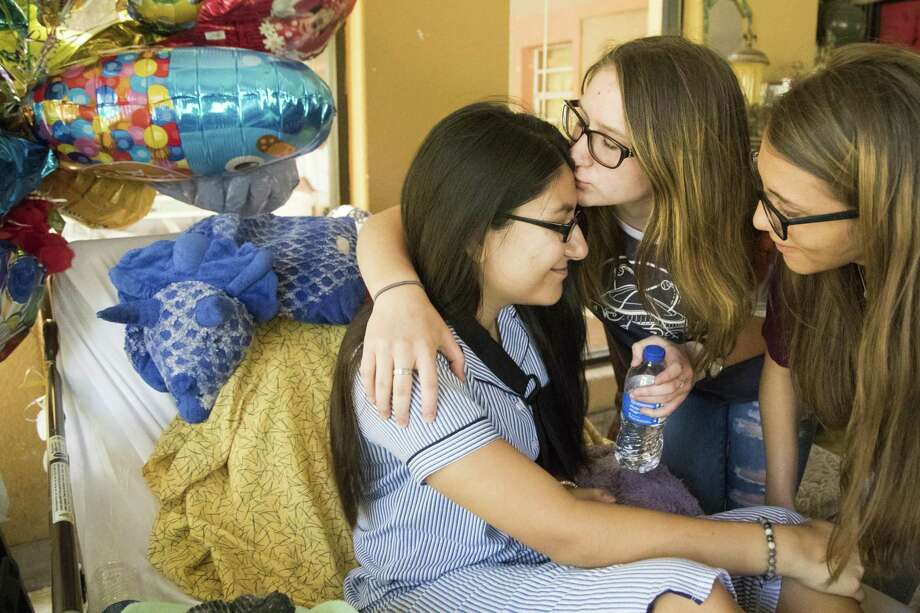 Emma Lovejoy, center, 15, kisses the forehead of her best friend Sarah Salazar, left, who got shot at Santa Fe High School  where they are students. Wednesday, June 6, 2018, in Santa Fe. ( Marie D. De Jesus / Houston Chronicle ) Photo: Marie D. De Jesus, Houston Chronicle / Houston Chronicle / © 2018 Houston Chronicle