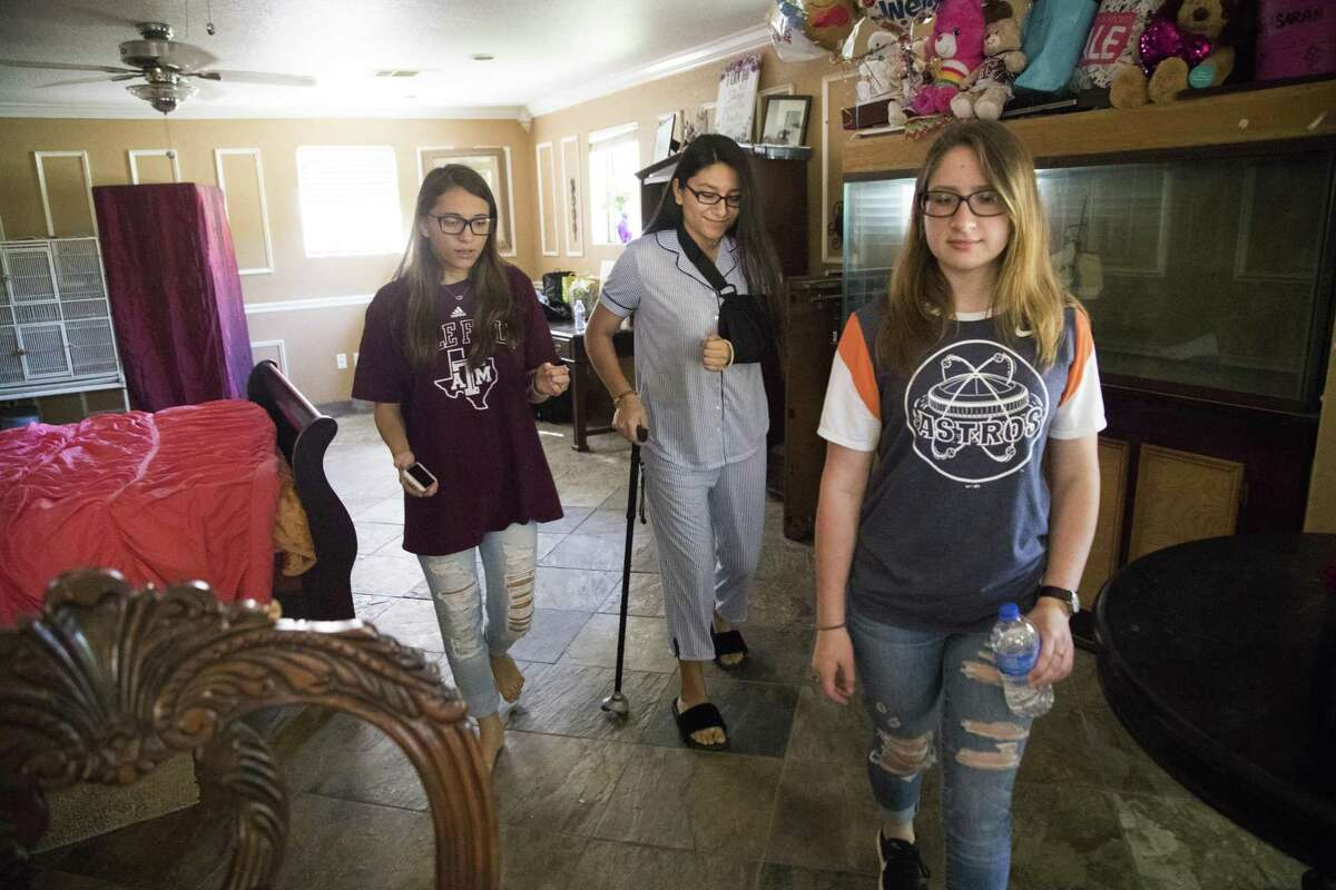 Santa Fe High School student Sarah Salazar, center, walks back to bed using a walking cane and accompanied by her two best friends, Brianna Huston, left, 15, and Emma Lovejoy, right, 15, on Wednesday, at Salazar's home in Santa Fe. Salazar was shot during a shooting at her high school and is recuperating from a shattered shoulder, a broken jaw and ribs. ( Marie D. De Jesus / Houston Chronicle )