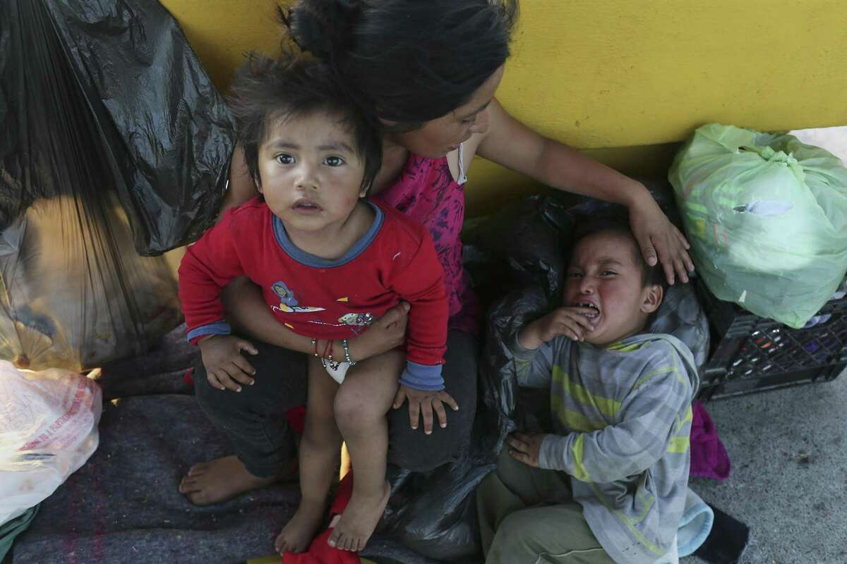 """Antonia Florinda Lopez Ixmata, 20, sits with her children, Erik Lopez, 2, and Aymer Damian Lopez, 4, on the Mexican side of the Roma-Ciudad Miguel Aleman International Bridge by Roma, Texas, Tuesday, June 5, 2018. They are Mayan descendants from Guatemala and have been waiting on the bridge for 8 days hoping for asylum in the United States. Amid this new era of a """"zero-tolerance"""" policy toward immigrants in the U. S., those seeking asylum through the United States' legal ports of entry --namely, the international bridges--are being denied entry. They've been told by agents that Department of Homeland Security facilities are overwhelmed."""