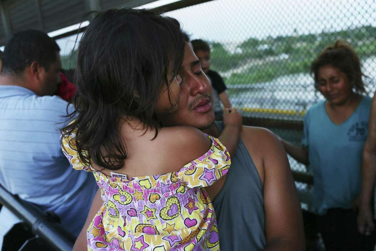 During prayer, Marco Estrada, 25, hugs his daughter, Violet, 2, on the Mexican side of the Roma-Ciudad Miguel Aleman International Bridge, Tuesday, June 5, 2018. More than 50 mostly Central American immigrants are camped at the bridge hoping for asylum in the United States. Estrada is hoping to join a cousin in North Carolina.