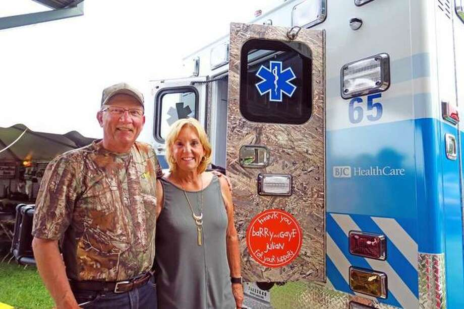 """Barry and Gaye Julian stand next to the latest """"Duck Plucker"""" ambulance, which honors their longtime support of the event. Photo:       For The Telegraph"""