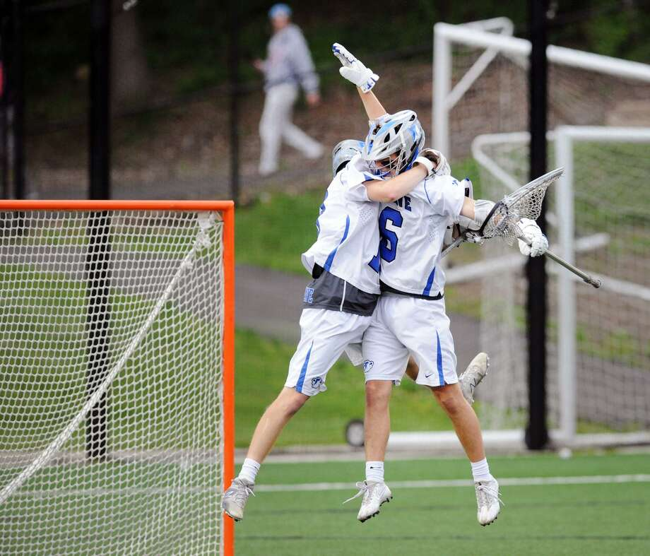 Sean Collins, left, the Darien goalie, and teammate Charlie Olsen, a defender, right, celebrate an 8-7 victory over New Canaan at the conclusion of the class L boys high school lacrosse semifinal match between New Canaan High School and Darien High School at Fairfield University, Conn., Wednesday, June 6, 2018. Photo: Bob Luckey Jr. / Hearst Connecticut Media / Greenwich Time