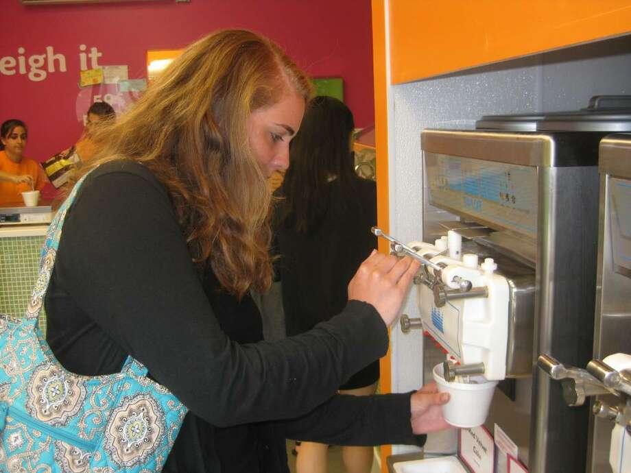 Elizabeth Toomey, 19, of Westport, swirls red velvet and alpine vanilla frozen yogurt at Top This, Westport's newest self-serve frozen yogurt shop. Photo: Contributed Photo, Contributed Photo / Alexander Laska / Westport News