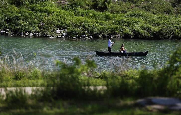 A couple makes their way along the San Antonio River in a canoe along Mission Reach. The 8-mile stretch of the San Antonio River offers more than 15 miles of trails.