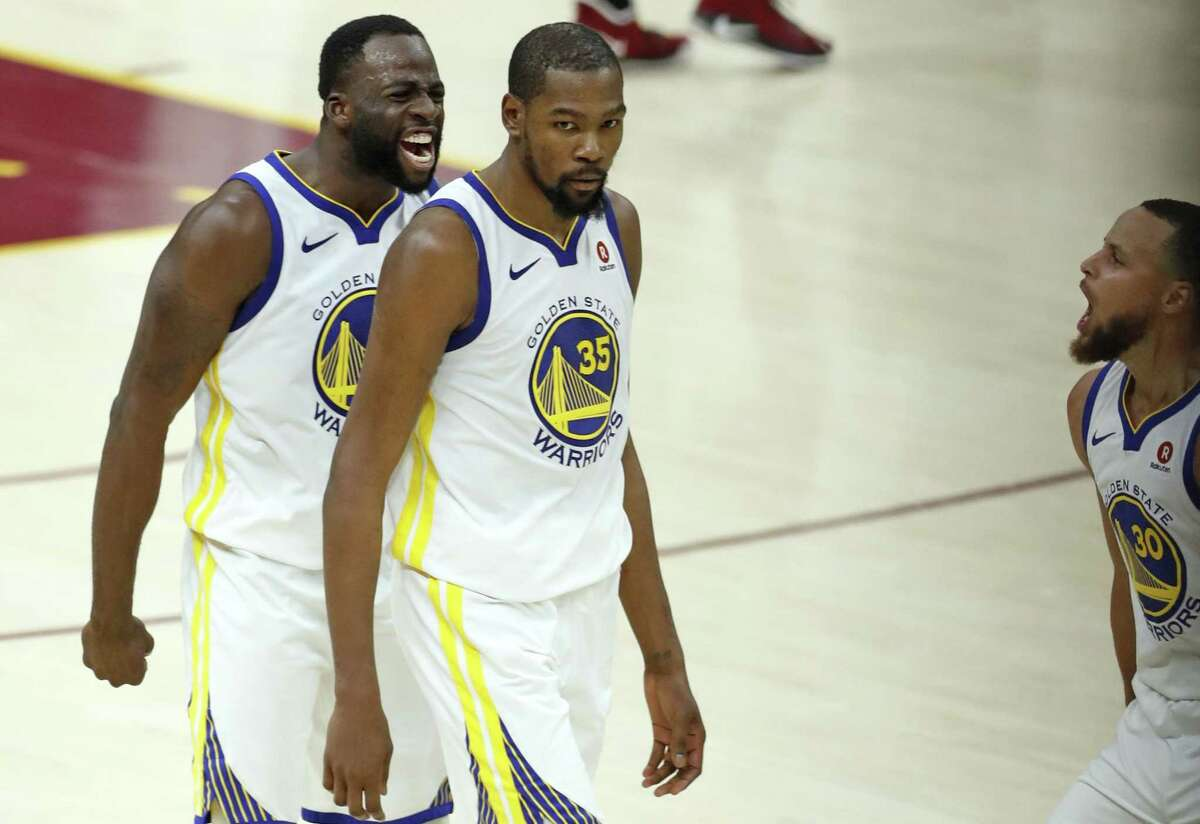 Golden State Warriors' Draymond Green and Stephen Curry react after Kevin Durant hit 3-pointer late in 4th quarter of Warriors' 110-102 win over Cleveland Cavaliers in Game 3 of the NBA Finals at Quicken Loans Arena in Cleveland, OH on Wednesday, June 6, 2018.