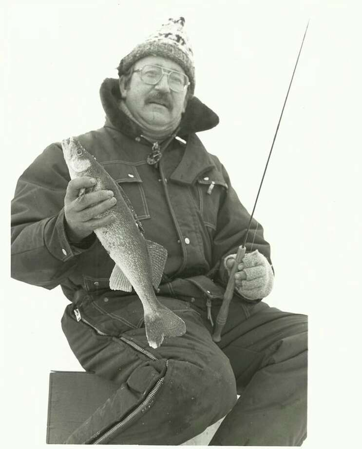 In this photo from the 1980s, DNR fisheries biologist Leo Mrozinski, who helped oversee the restoration of walleye populations in Saginaw Bay, displays a winter-caught product of that work on the Bay off Kawkawlin. DNR officials say last winter's Bay anglers set records for angling effort and walleye catches. (Steve Griffin file photo/for Hearst Michigan)