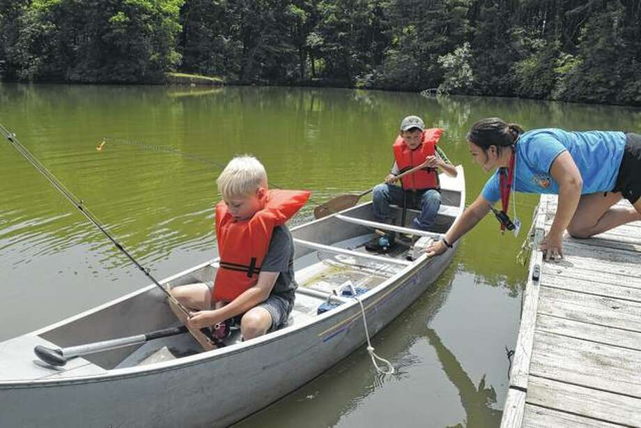 Western Illinois Youth Camp campers Ruger York (left), 7, and Drake Dyche, 9, get a shove off Wednesday from camp counselor Bentley Stewart as they go on a fishing expedition at Lake Jacksonville.