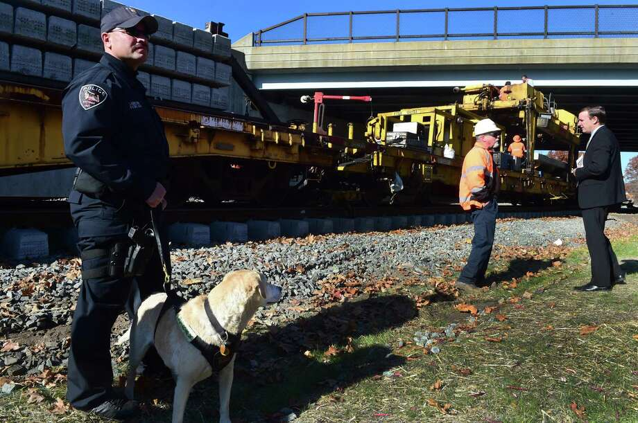 "U.S. Senator Christopher Murphy, right, talks with an Amtrak supervisor under the protective eye of Amtrak Police Officer Joseph E. Agnellino and his K-9 partner Roxy Monday morning, November 14, 2016. as Murphy visits the New Haven-Hartford-Springfield Rail Line near North Colony Road in Wallingford to receive an update on the progress of the rail line and observe the ""track construction machine"" which is building a second track parallel to the existing single track used by Amtrak trains. This double-tracking will allow more frequent train service and make for easier commuter rail serve between New Haven, Hartford, and Springfield. Service will begin June 16, 2018. Photo: Peter Hvizdak / ©2016 Peter Hvizdak / ©2016 Peter Hvizdak"