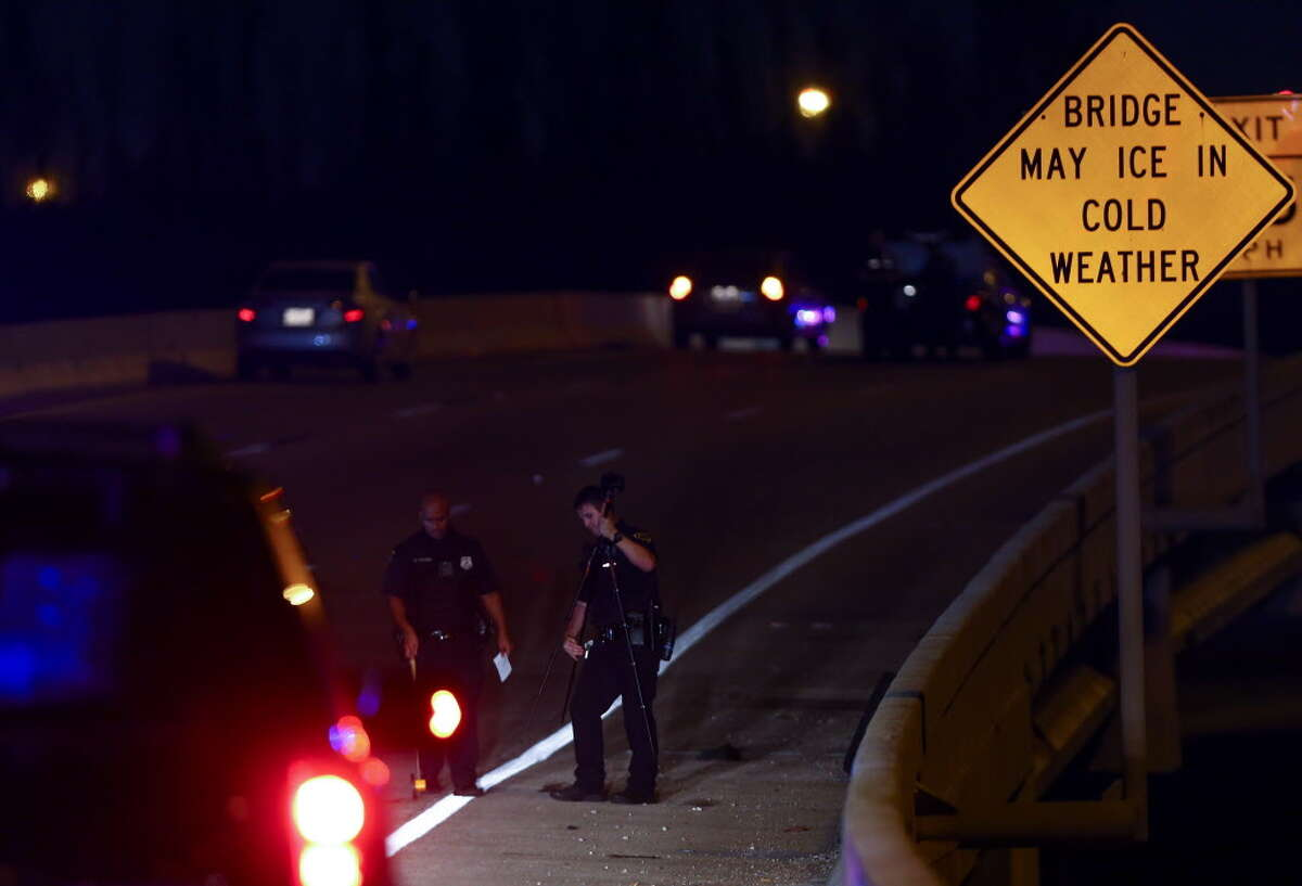 Houston Police officers investigate the scene where a man was struck by a motorist while crossing the North 610 Freeway exit ramp off the northbound Eastex Freeway Thursday, June 7, 2018, in Houston.