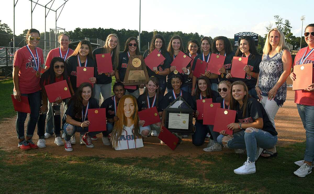 The Atascocita Lady Eagles show off their Class 6A State Softball Championship trophy during the ?