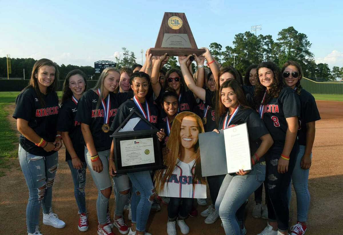 The Atascocita Lady Eagles show off their Class 6A State Softball Championship trophy during the