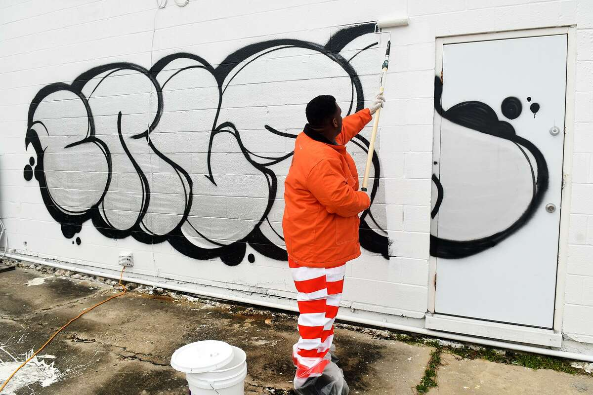 Inmates from the Harris County Jail remove graffiti from a business on FM 1960 on Feb. 5, 2018. Harris County Sheriff's Office is reminding residents to report possible signs of organized criminal activity in their neighborhoods.